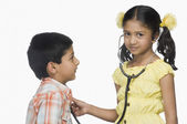 Girl examining a boy with a stethoscope — Stock Photo