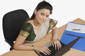Businesswoman working on a laptop in an office — Stock Photo