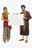 Sikh couple holding a blank placard — Stock Photo