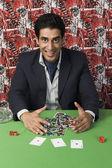 Man collecting won gambling chips — Stock Photo