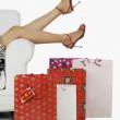 Woman on a couch surrounded by shopping bags — Stock Photo