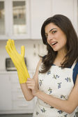 Woman wearing rubber gloves — Stockfoto