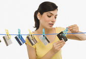 Woman hanging credit cards on a clothesline — Stock Photo