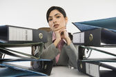 Stack of ring binders in front of a businesswoman — Stock Photo