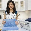 Woman folding laundry — Stock Photo
