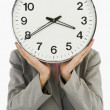 Businesswoman hiding her face with a clock — Foto Stock
