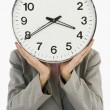 Businesswoman hiding her face with a clock — Stockfoto #33002747