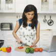 Woman chopping tomatoes in the kitchen — Stock Photo