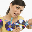 Stock Photo: Womhanging CDs on clothesline