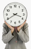 Businesswoman hiding her face with a clock — Stock Photo