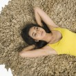 Woman lying on a rug — Stock Photo