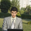 Businessman using a laptop in a park — Stock Photo