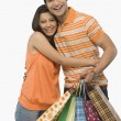 Woman hugging a man holding shopping bags — Stock Photo