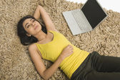 Woman lying on a rug with a laptop — Stock Photo