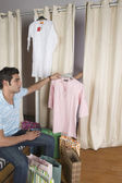 Man giving a kurta to a woman to try on in a store — Stock Photo