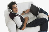 Man listening to headphones while using a laptop — Stock Photo