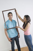Woman holding a picture frame in front of a man — Stock Photo