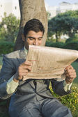 Businessman reading a newspaper in a park — Стоковое фото