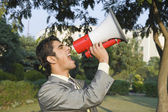 Businessman shouting into a megaphone — Stock Photo