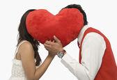 Couple romancing behind a heart shape — Stock Photo