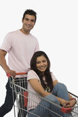 Woman sitting in shopping cart — Stock Photo