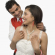 Man putting the necklace in his girlfriend's neck — Stock Photo #33031385