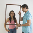 Man holding a picture frame in front of a woman — Stok fotoğraf