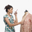 Fashion designer trying a dress on a mannequin — Stock Photo