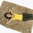 Stock Photo: Womlying on rug