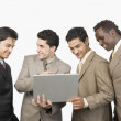Four businessmen standing with a laptop — Stock Photo