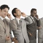 Four businessmen talking on mobile phones — Stock Photo