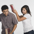 Woman beating her friend with a book — Stock Photo