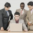 Businessmen looking at their colleague using a laptop — Stock Photo