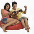 Couple playing a video game on a bean bag — Stock Photo