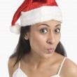 Woman wearing a Santa hat and puckering — Stock Photo