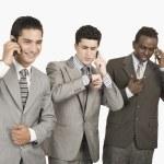 Three businessmen talking on mobile phones — Stock Photo