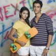 Couple standing with a skateboard — Stok fotoğraf
