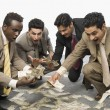 Stock Photo: Businessmen crouching and holding currency notes