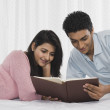 Couple reading a book on the bed — Stock Photo