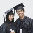 Couple in graduation gowns holding diplomas — Stock Photo