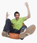 Man cheering on a bean bag — Stock Photo