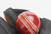 Cricket ball on a wicket keeping glove — Stock Photo