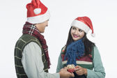 Man giving Christmas present to a woman — Stock Photo