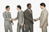 Four businessmen shaking hands — Stock Photo