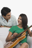 Woman playing a guitar beside his boyfriend — Stock Photo