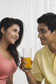 Man holding a glass of orange juice and looking at his girlfriend — Stock Photo