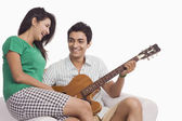 Man playing a guitar beside a woman — Stock Photo