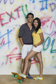Couple standing with a skateboard in front of a graffiti covered wall — Stock Photo