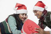 Couple lying on a floor with a Christmas present — Stock Photo