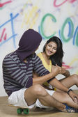 Couple sitting with a skateboard — Stock Photo